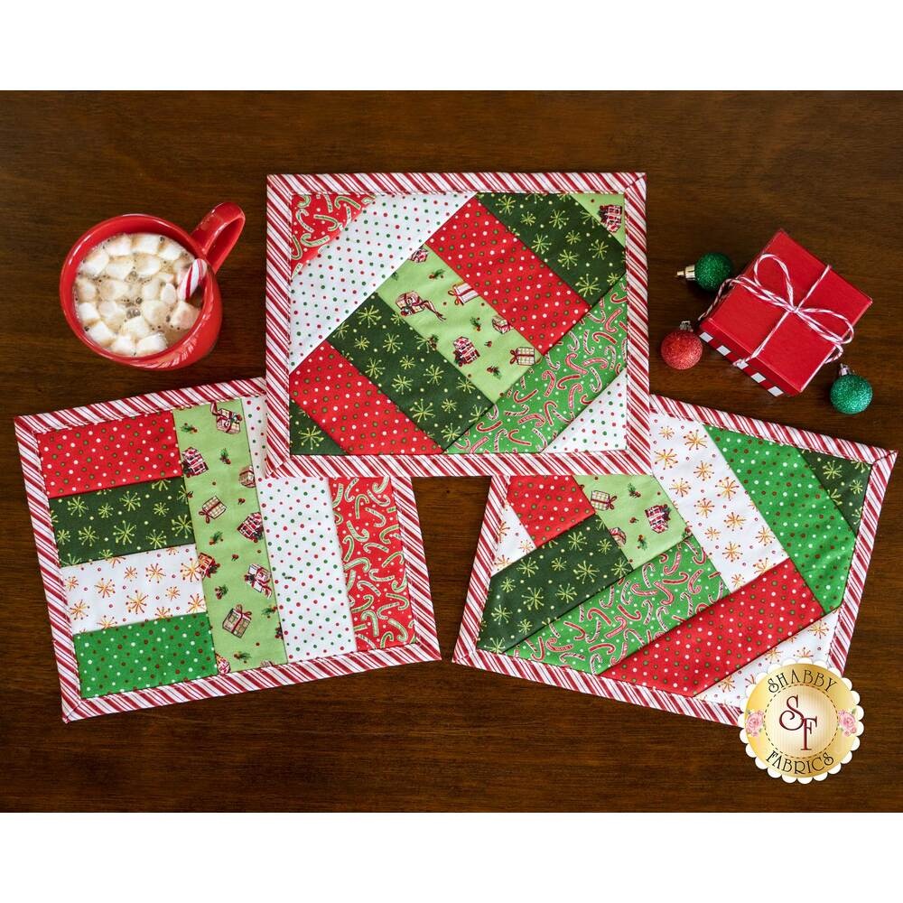 """Three 2.5"""" Strip Mug Mats in the All The Trimmings collection displayed on a table 