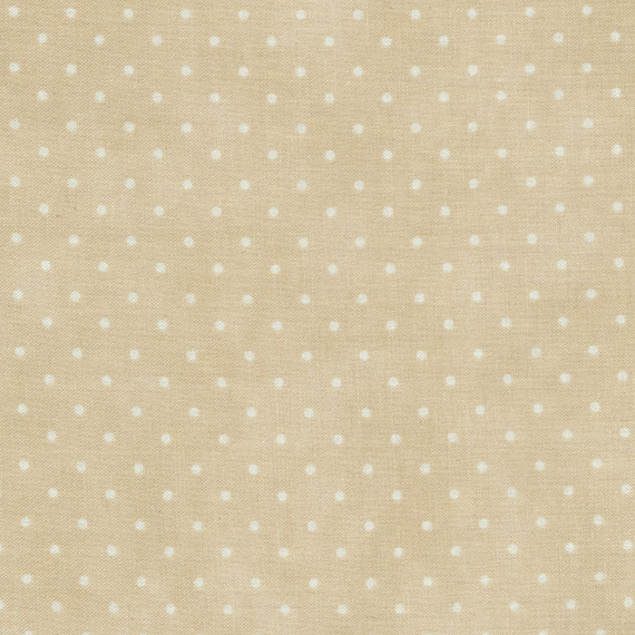 White polka dots on a tan background