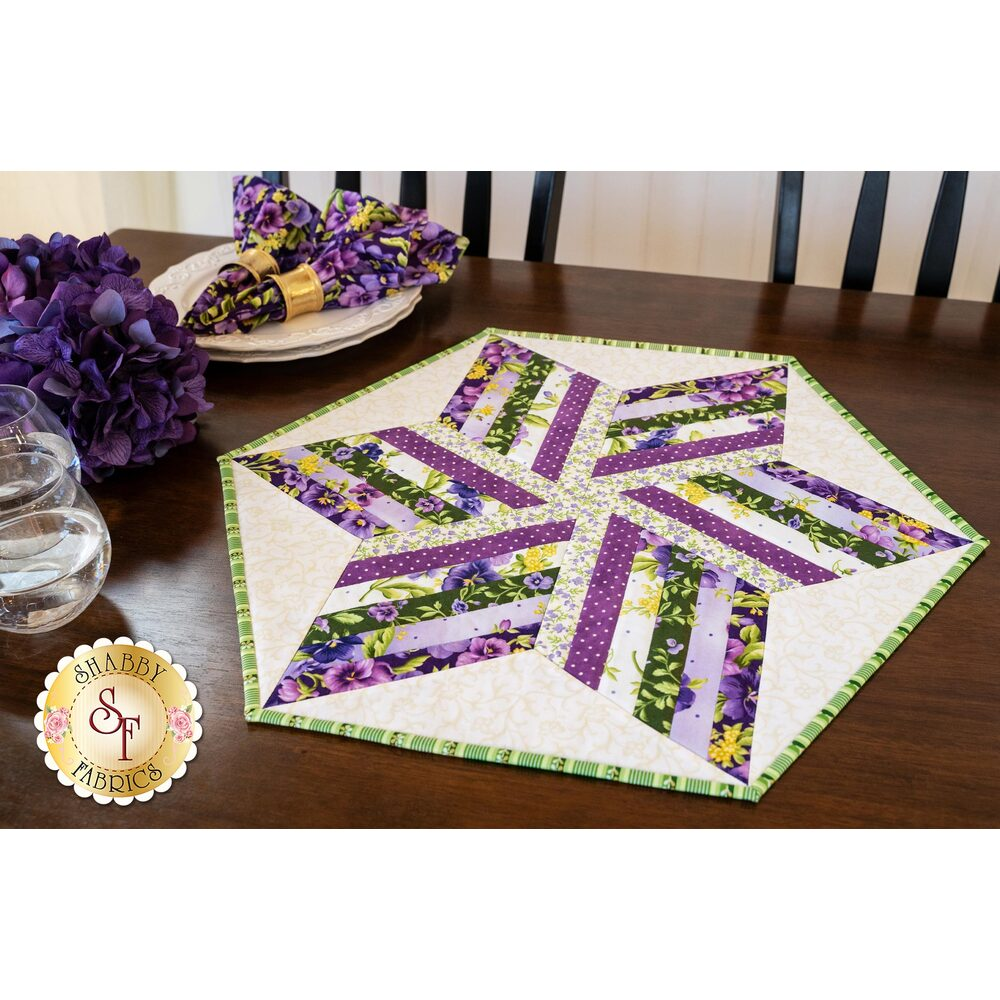 Purple, green, and yellow six-pointed star shape on cream hexagon table topper.