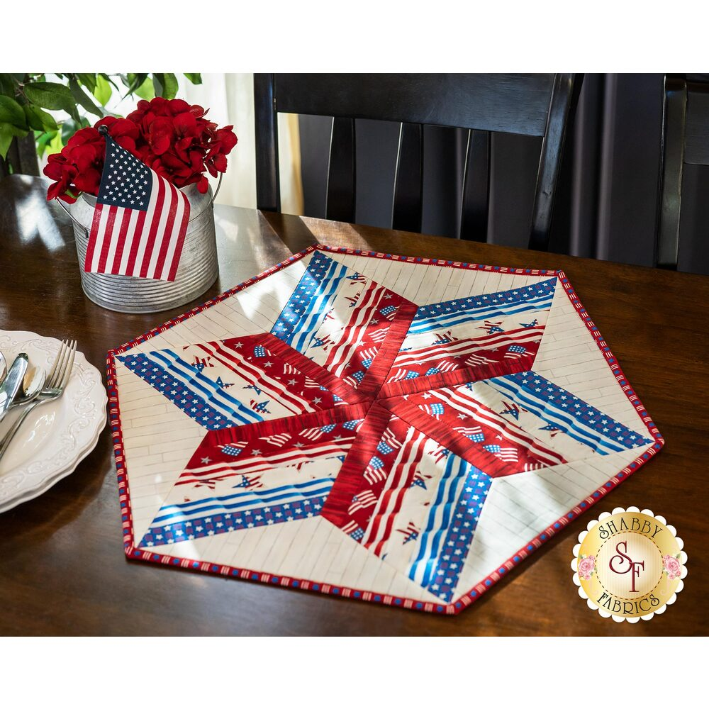 Patriotic red, white, and blue 60 degree table topper on a wood table