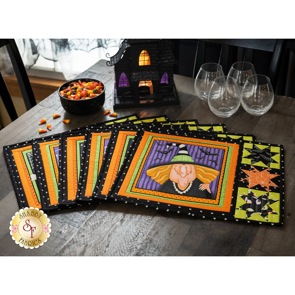 6 Halloween themed Placemats on a dark rustic with candy corn and a haunting house