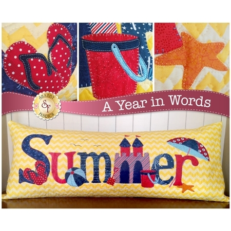 Kit for July A Year In Words pillow reading Summer with a sandcastle and yellow beach.