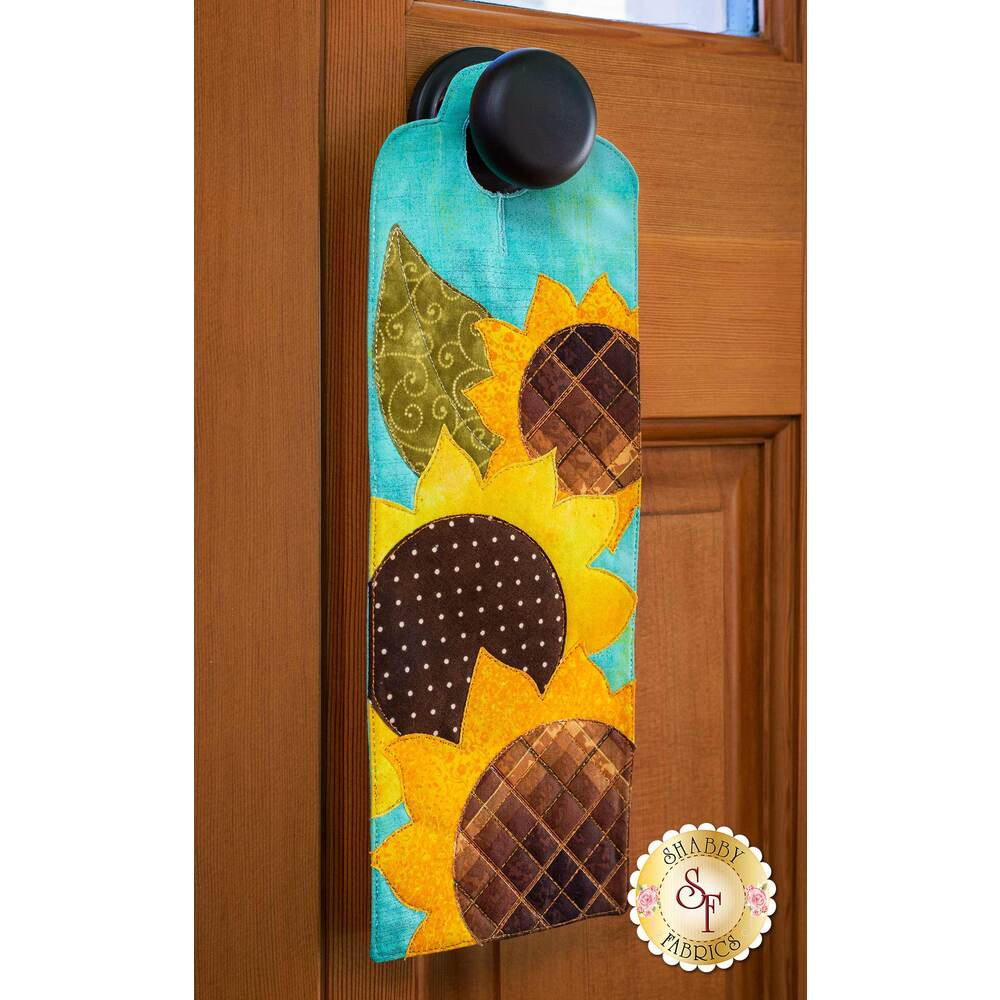 Door hanger kit for A-door-naments August with three yellow sunflowers on teal fabric.