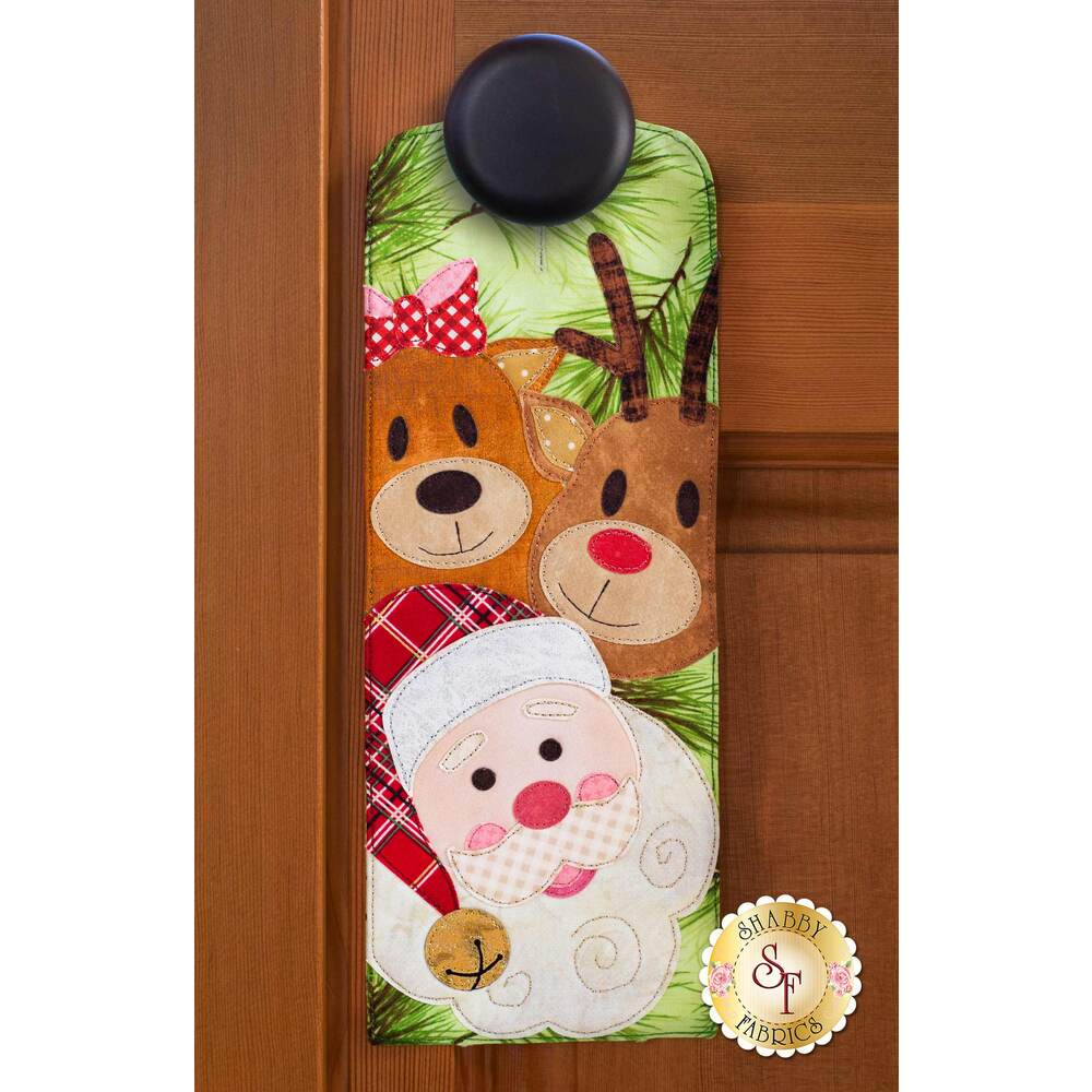 Door hanger kit for A-door-naments December with two reindeer and Santa on green fabric.
