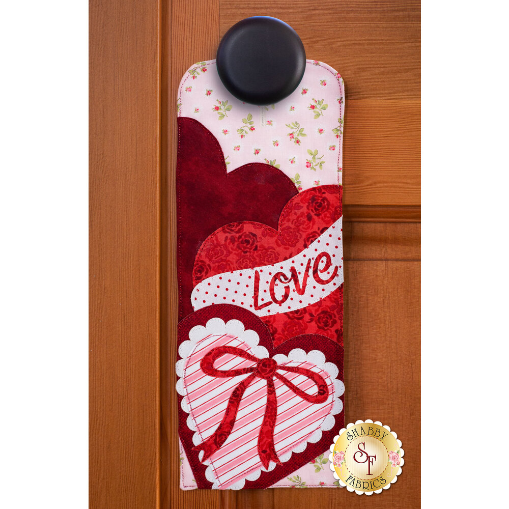 Door hanger kit for A-door-naments February with a wrapped heart-shaped box of chocolates.