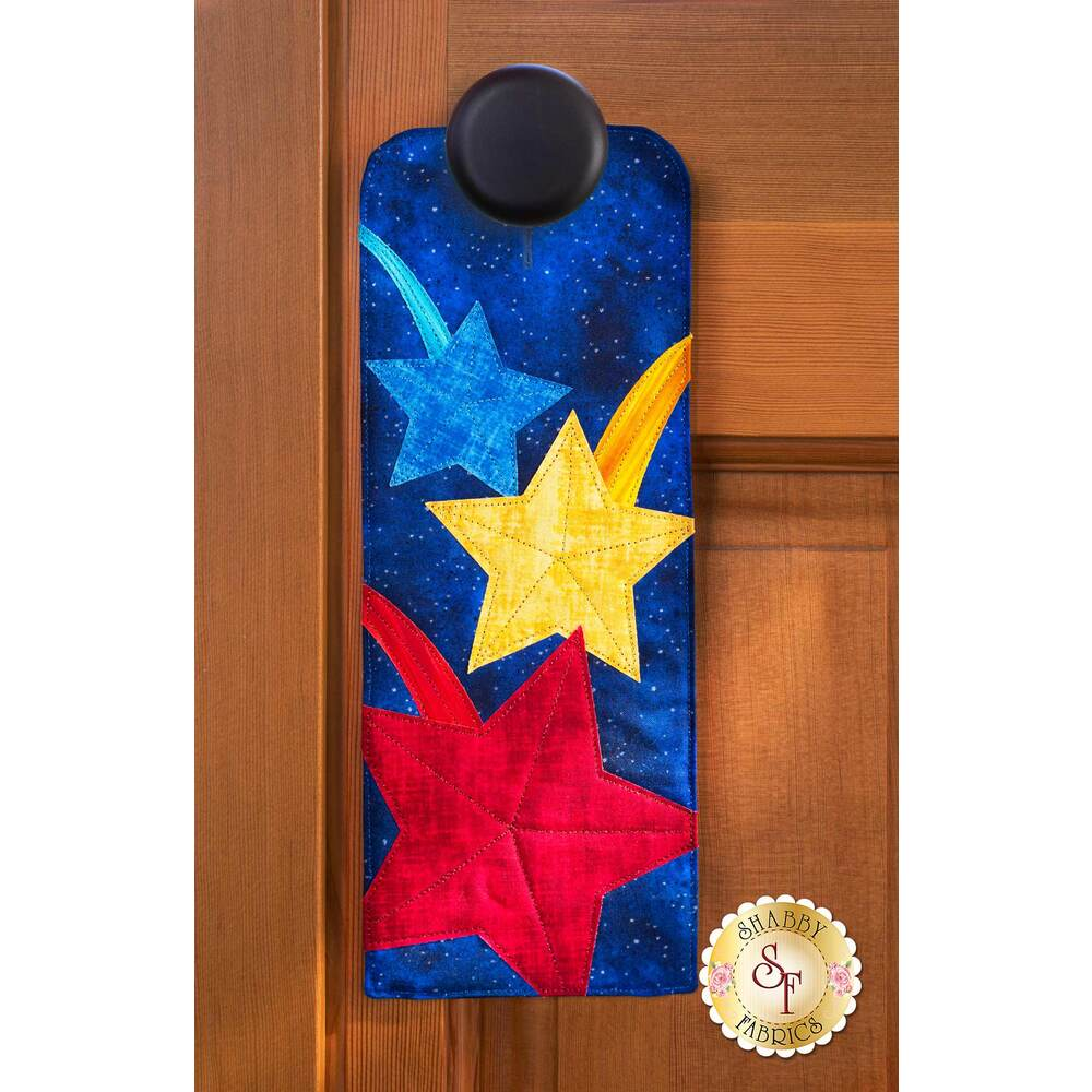 Door hanger kit for A-door-naments July with blue, yellow, & red shooting stars on deep blue fabric.