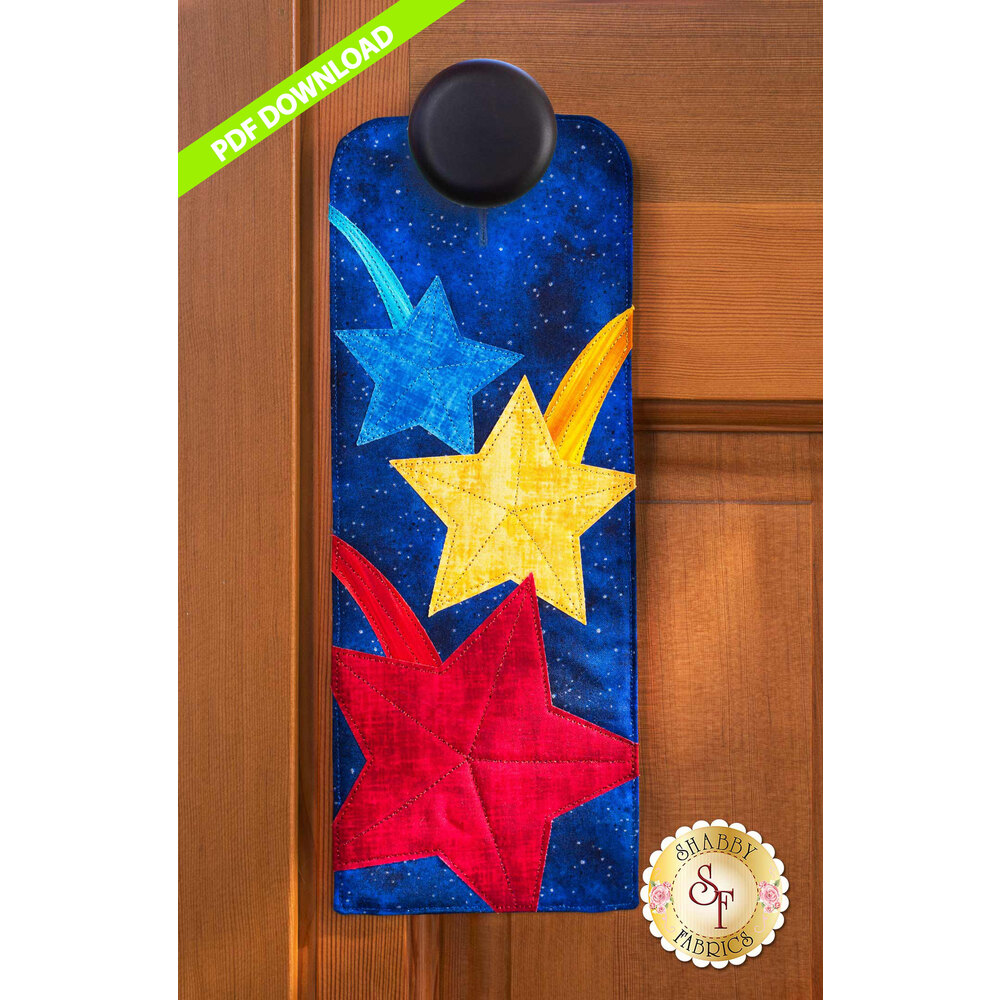 PDF Pattern for A-door-naments July with blue, yellow, & red shooting stars on deep blue fabric.