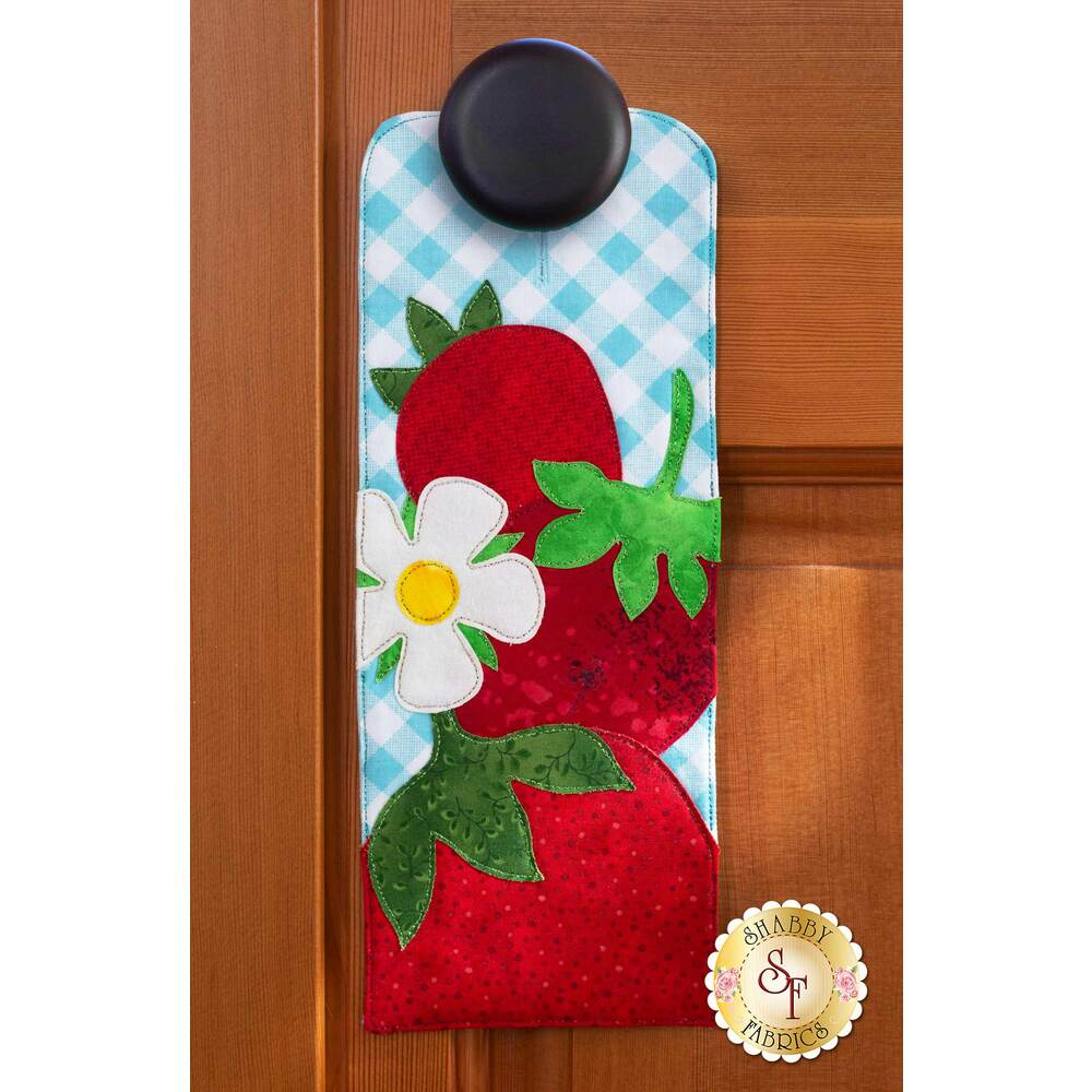Door hanger kit for A-door-naments June with three red strawberries and strawberry blossom on blue.