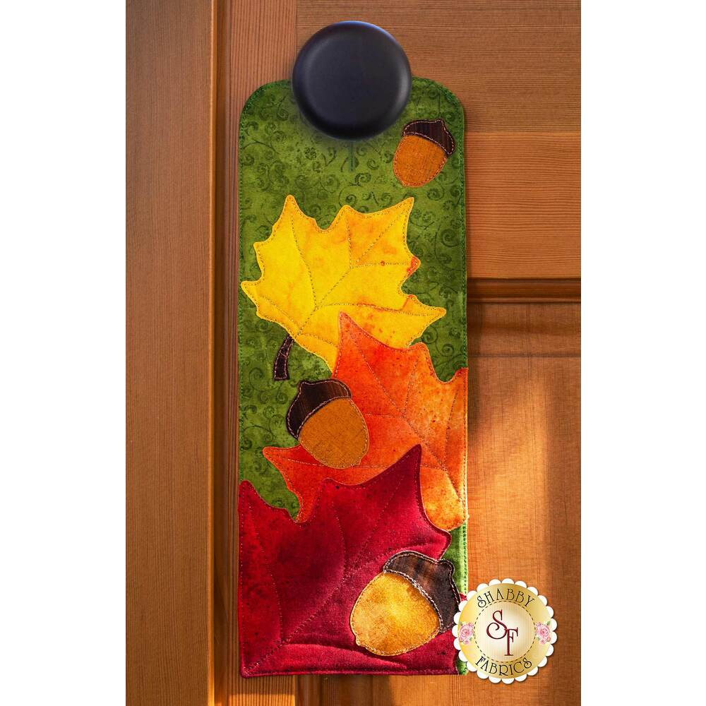 Door hanger kit for A-door-naments November with autumn leaves and acorns on green fabric.