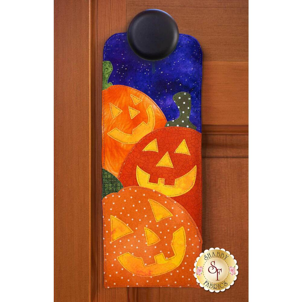 Door hanger kit for A-door-naments October with three smiling jack-o-lanterns on violet fabric.