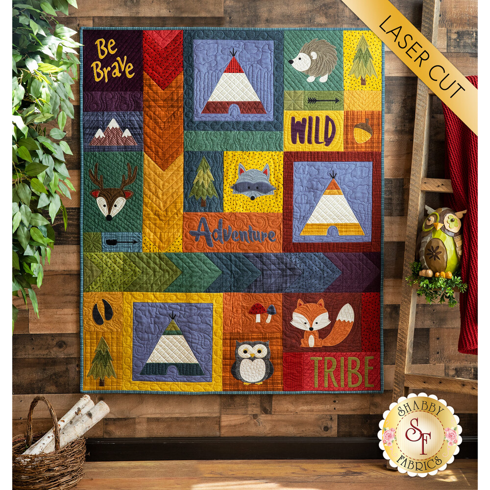 The adorable Adventure With My Tribe Quilt hung from a wooden wall