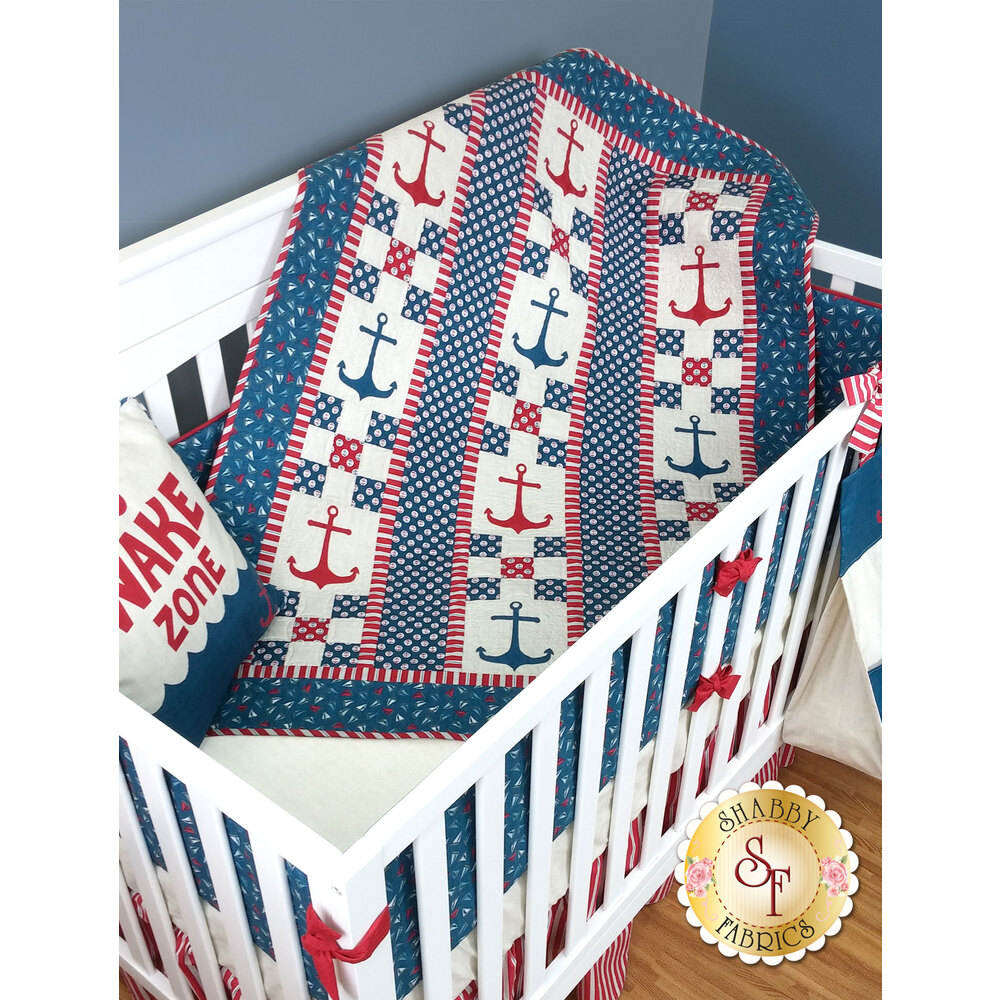 Red and blue nautical themed pieced quilt with staggered anchor applique shapes.