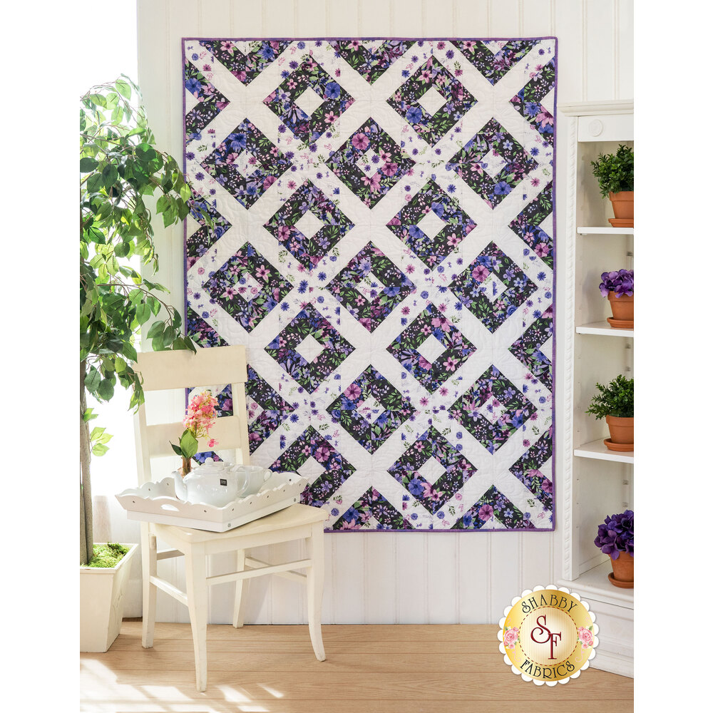 The gorgeous Amethyst Magic quilt displayed hanging on a wall