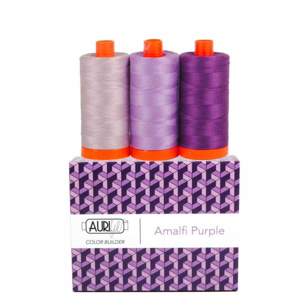 A spool of light, medium, and dark purple thread on an Aurifil Colorbuilder box