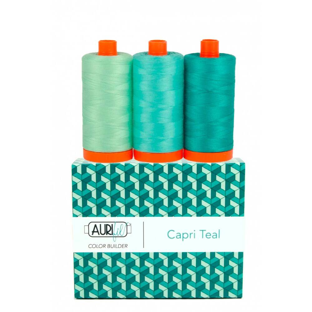 A spool of aqua, turquoise, and dark teal thread on an Aurifil Colorbuilder box