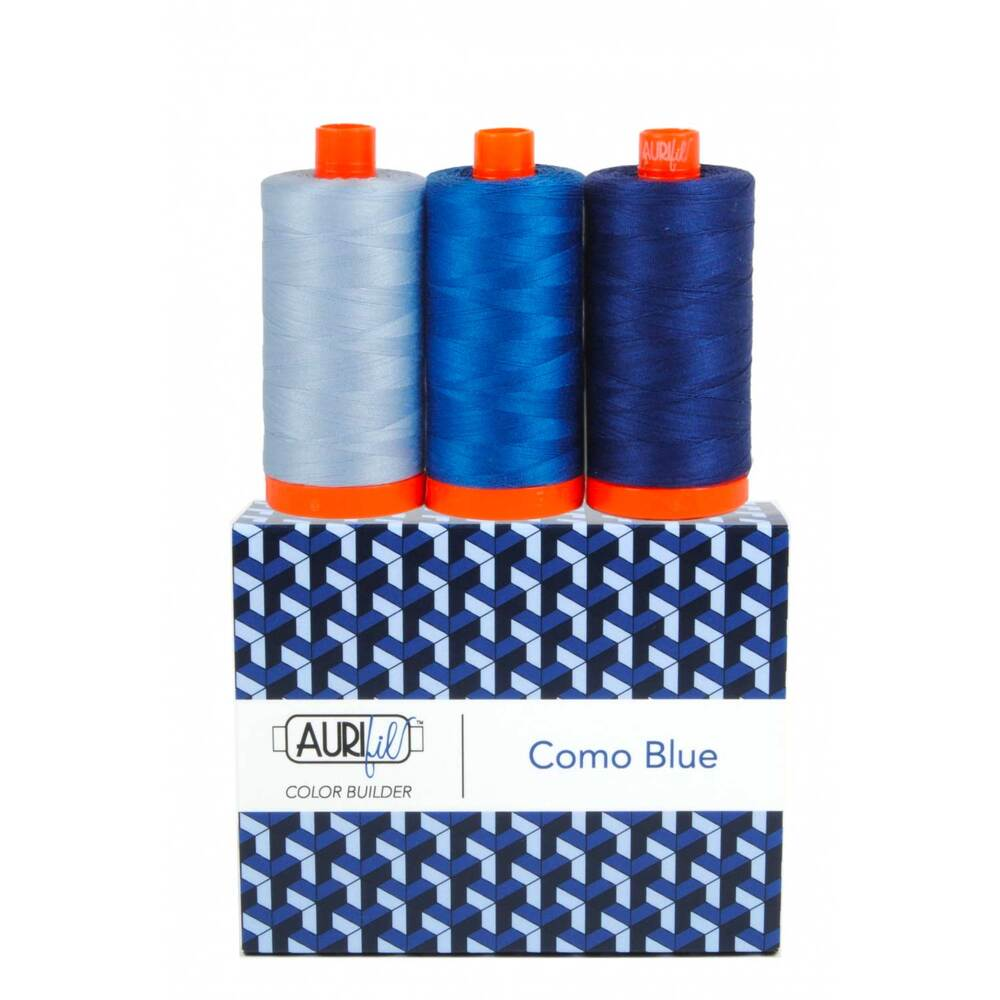 A spool of light, medium, and dark blue thread on an Aurifil Colorbuilder box