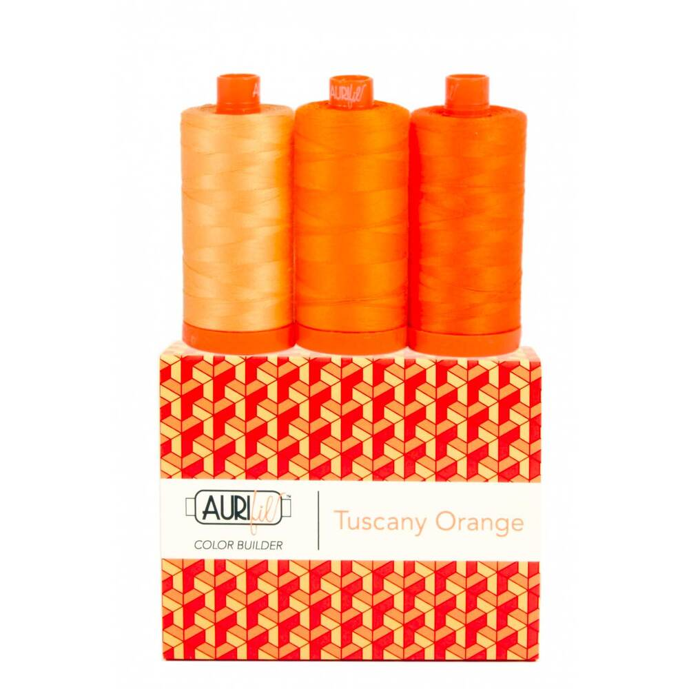 A spool of light, medium, and dark orange thread on an Aurifil Colorbuilder box