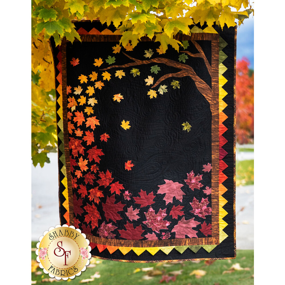 Quilt kit featuring brightly colored applique autumn leaves in a gradient on a black background.