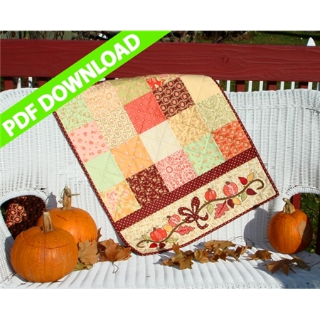 Table runner made from orange and pale brown patchwork squares with pumpkin vine applique on end.