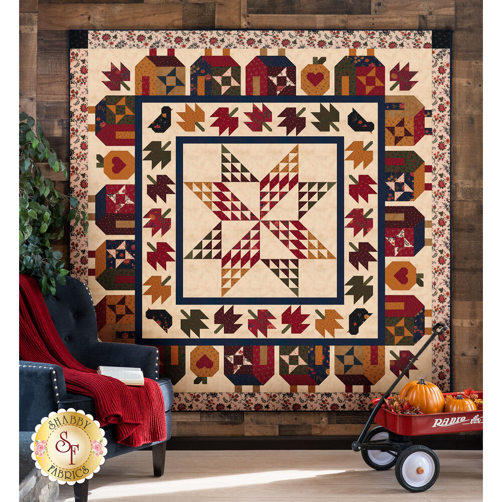 Geometric autumn themed quilt hung from a wall