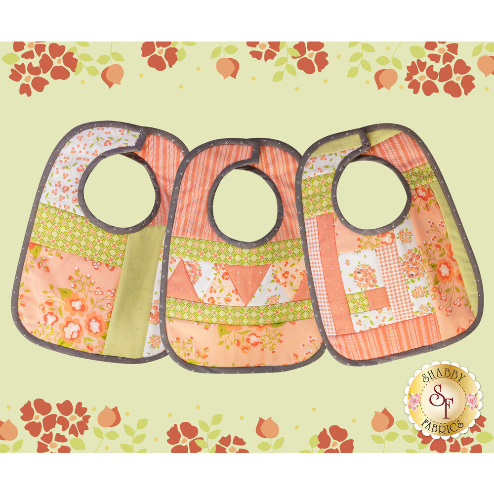 The three Baby Bibs made with Apricot & Ash fabrics on a green background