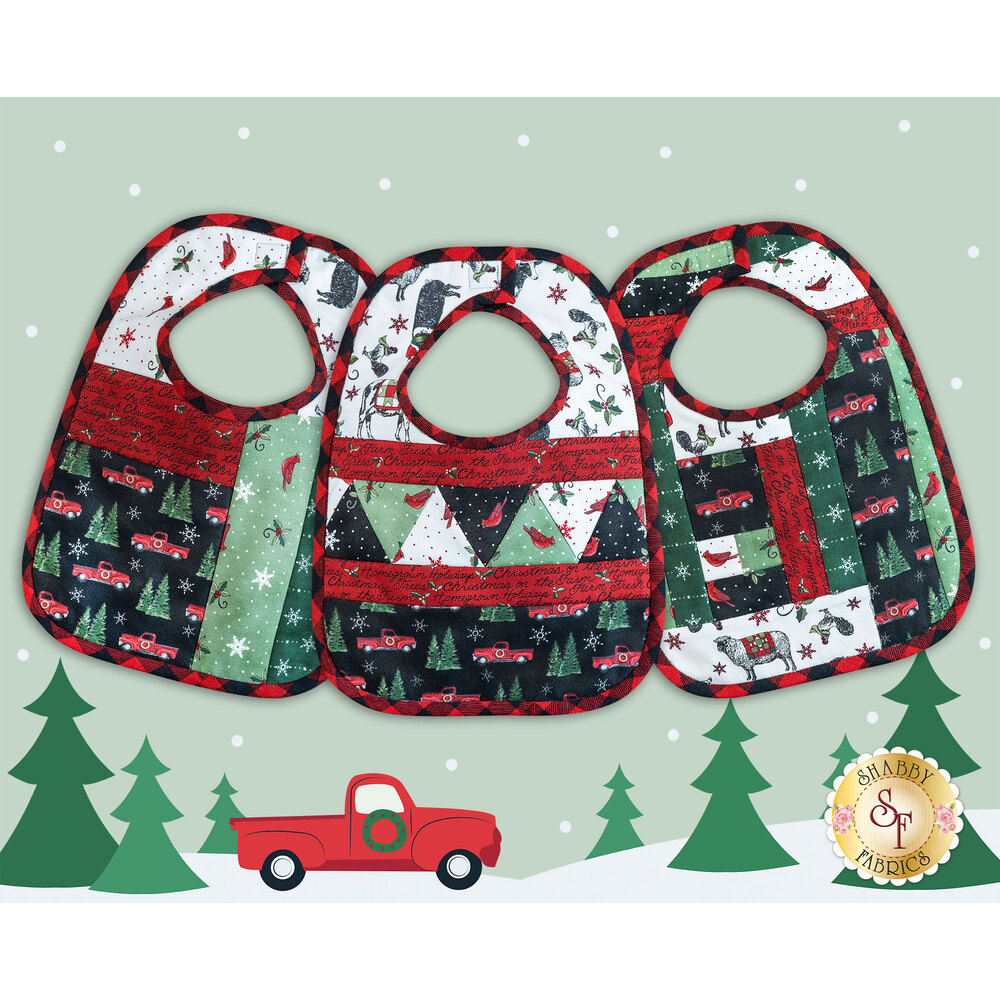 Three adorable Christmas baby bibs on a fun vintage truck background