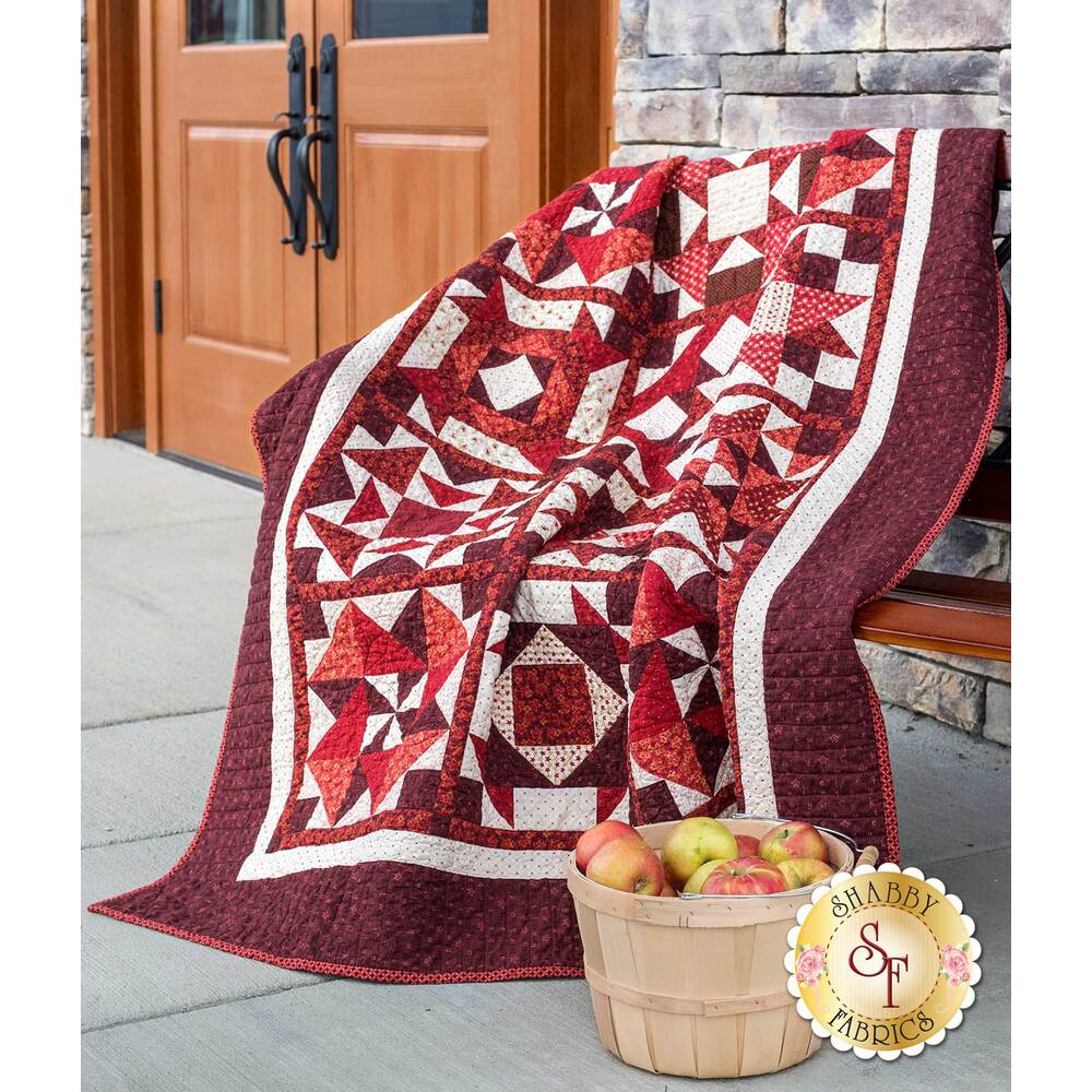 Wide shot of red and burgundy patchwork quilt draped over bench.
