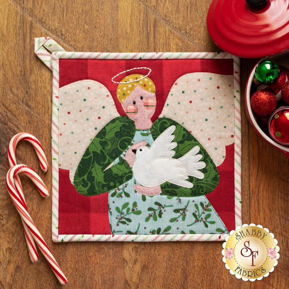 Adorable pot holder with a laser cut applique angel holding a dove on a wood table