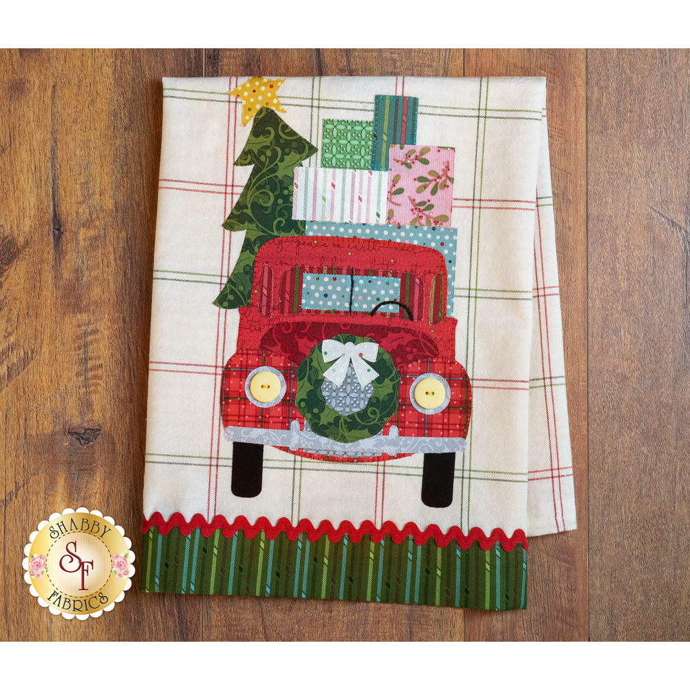 Tea towel with a laser cut vintage truck carrying Christmas presents hung from clothes pins