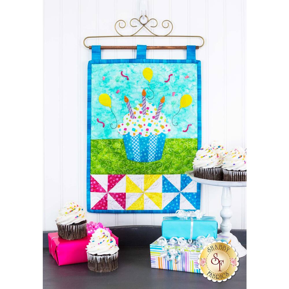 Cheerful birthday wall hanging featuring a cupcake with candles and balloons.