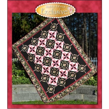 Black and pink pieced patchwork quilt with floral accents.