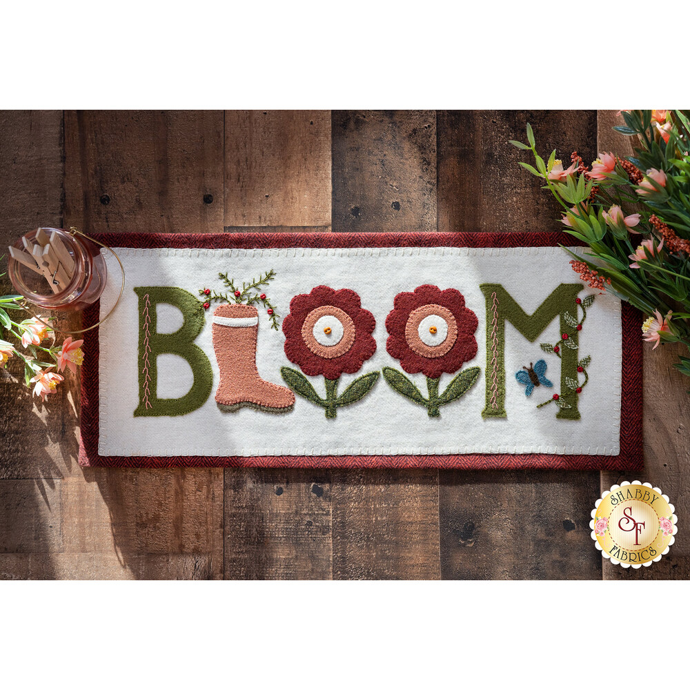 The adorable Bloom Where You're Planted mat displayed on a wood table | Shabby Fabrics