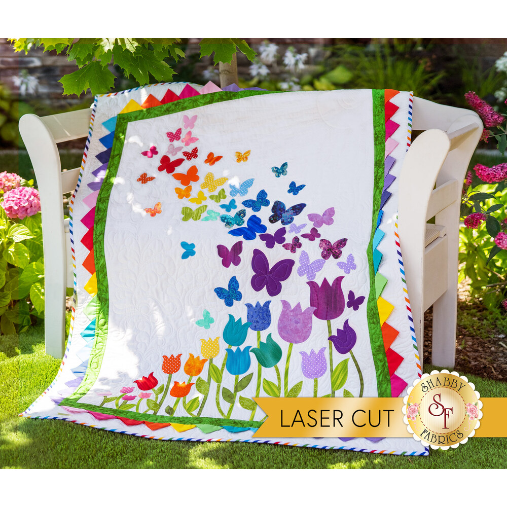 The beautiful Blooming Butterflies quilt draped over a chair outside | Shabby Fabrics