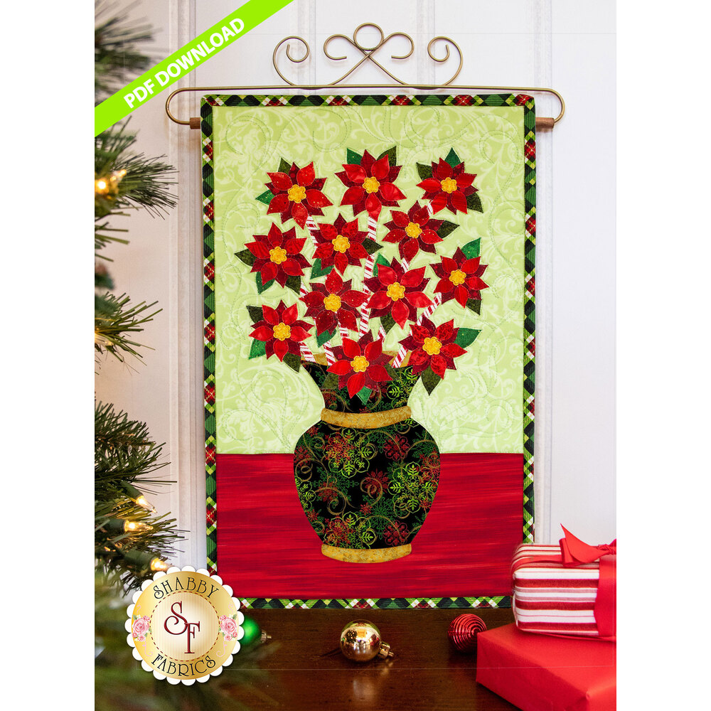 Vivid red poinsettias on peppermint stick stems in a textured green vase on a pale green background.