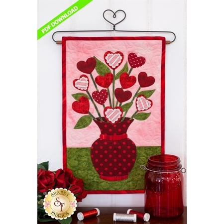 Deep red polka-dotted vase filled with red and pink hearts on stems.