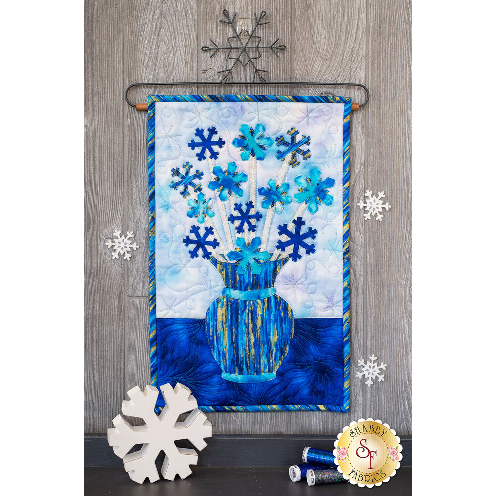 Blue snowflakes on white stems in a blue streaked vase.