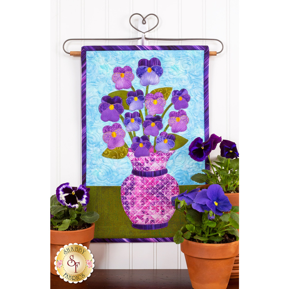 Pink geometric vase filled with purple pansies on blue background.