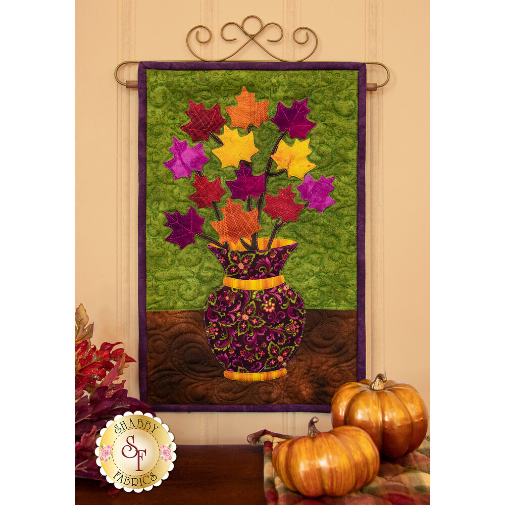 Red, orange, yellow, and purple leaves on branches in a textured purple vase.