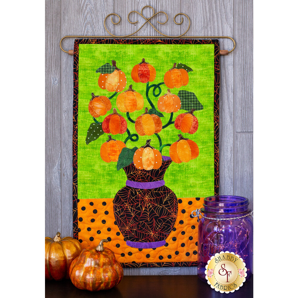 Pumpkins on a curved vine in a black spiderweb vase on a lime green and orange polka-dot background.