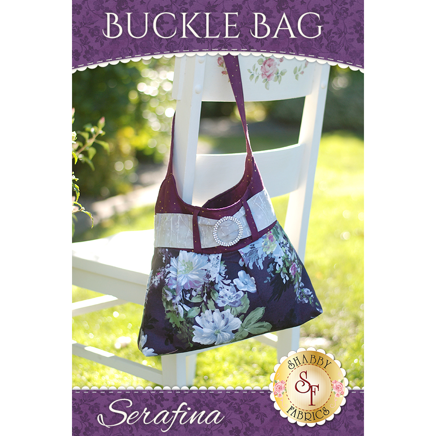 Medium-large handbag in purple and dark floral fabrics with central rhinestone buckle.