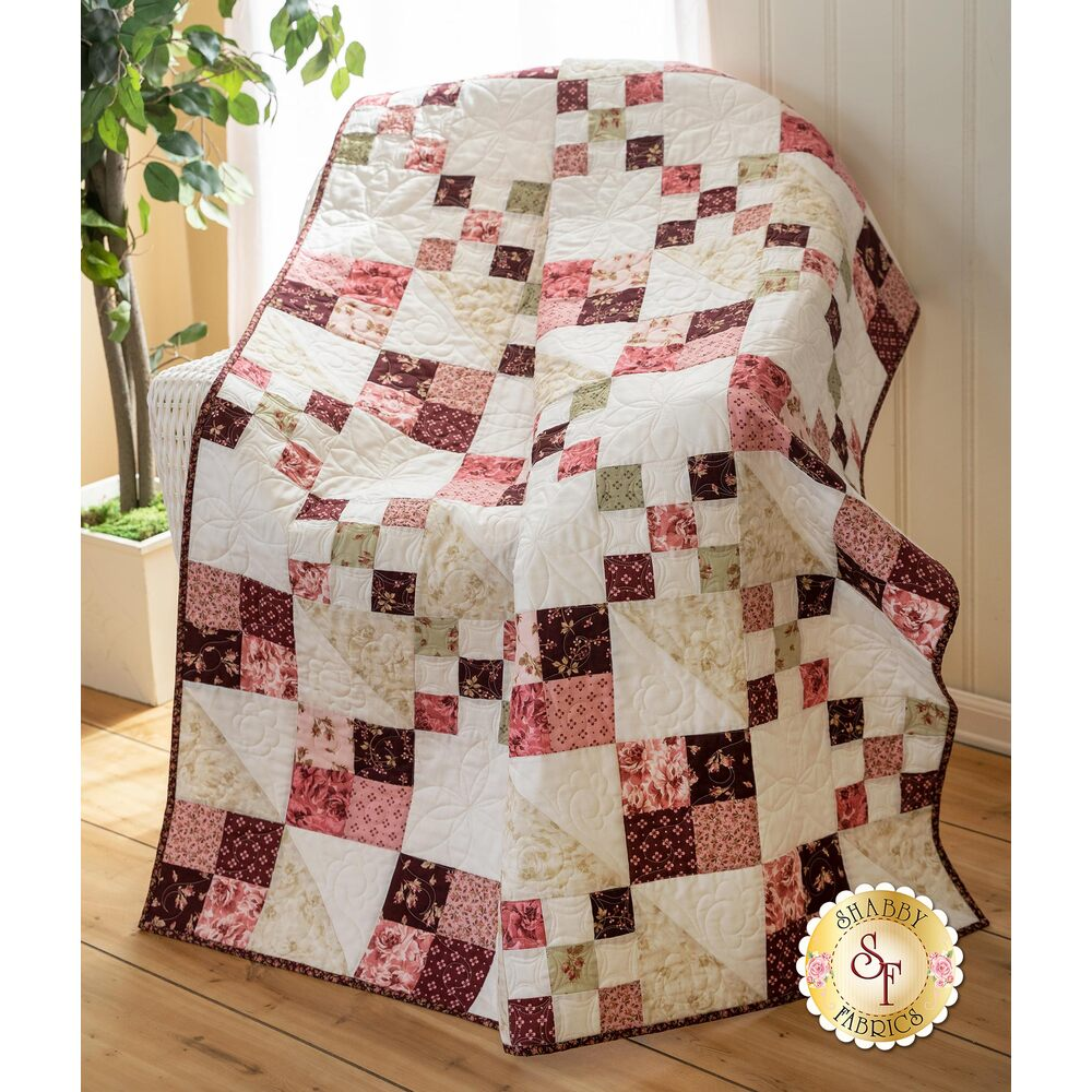 A beautiful red and cream pieced quilt draped over a chair