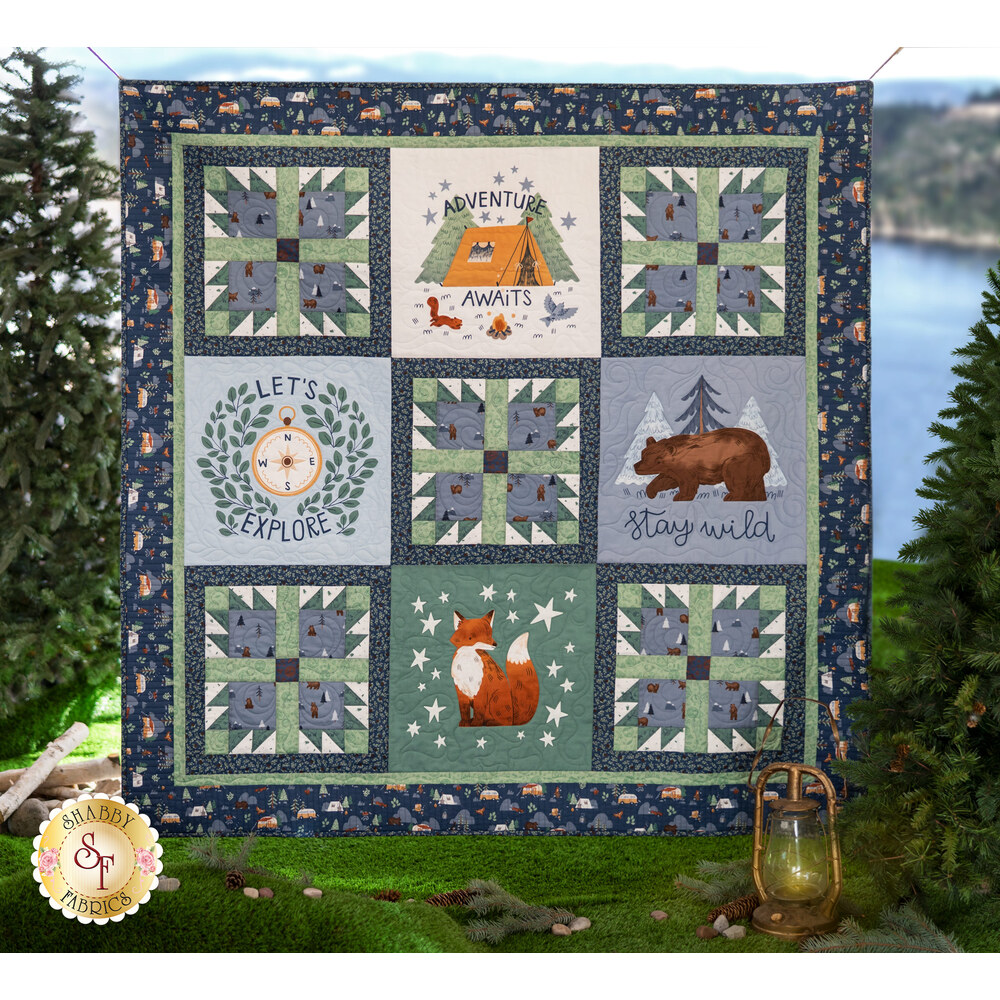 The Camp Woodland Quilt displayed in front of a lake