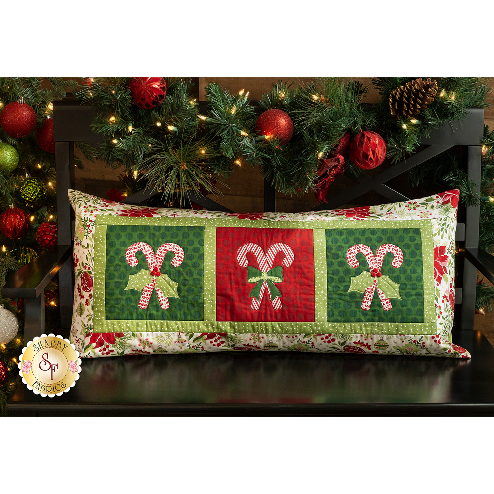 An adorable bench pillow with crossed candy canes under a tree