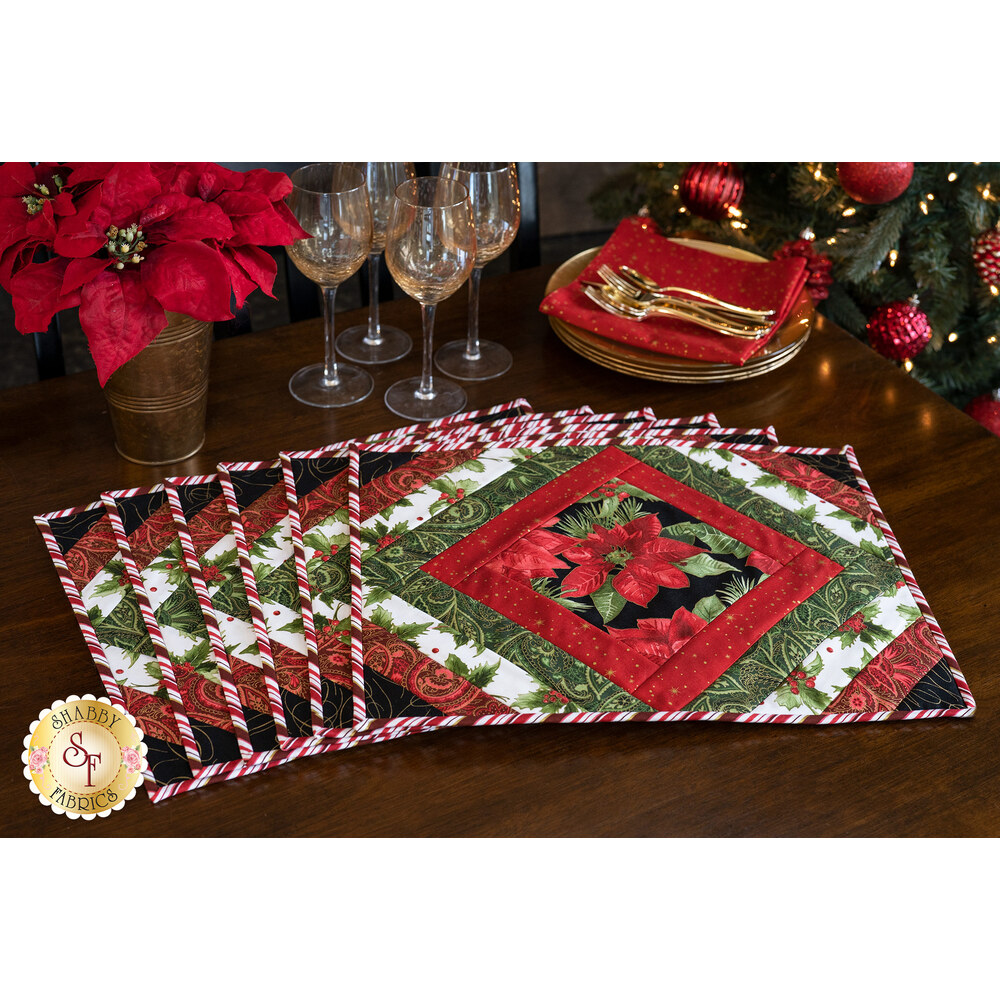 Six beautiful Christmas placemats fanned on a wood table