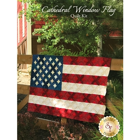 Cathedral Window style American flag quilt hanging on a wooden fence.