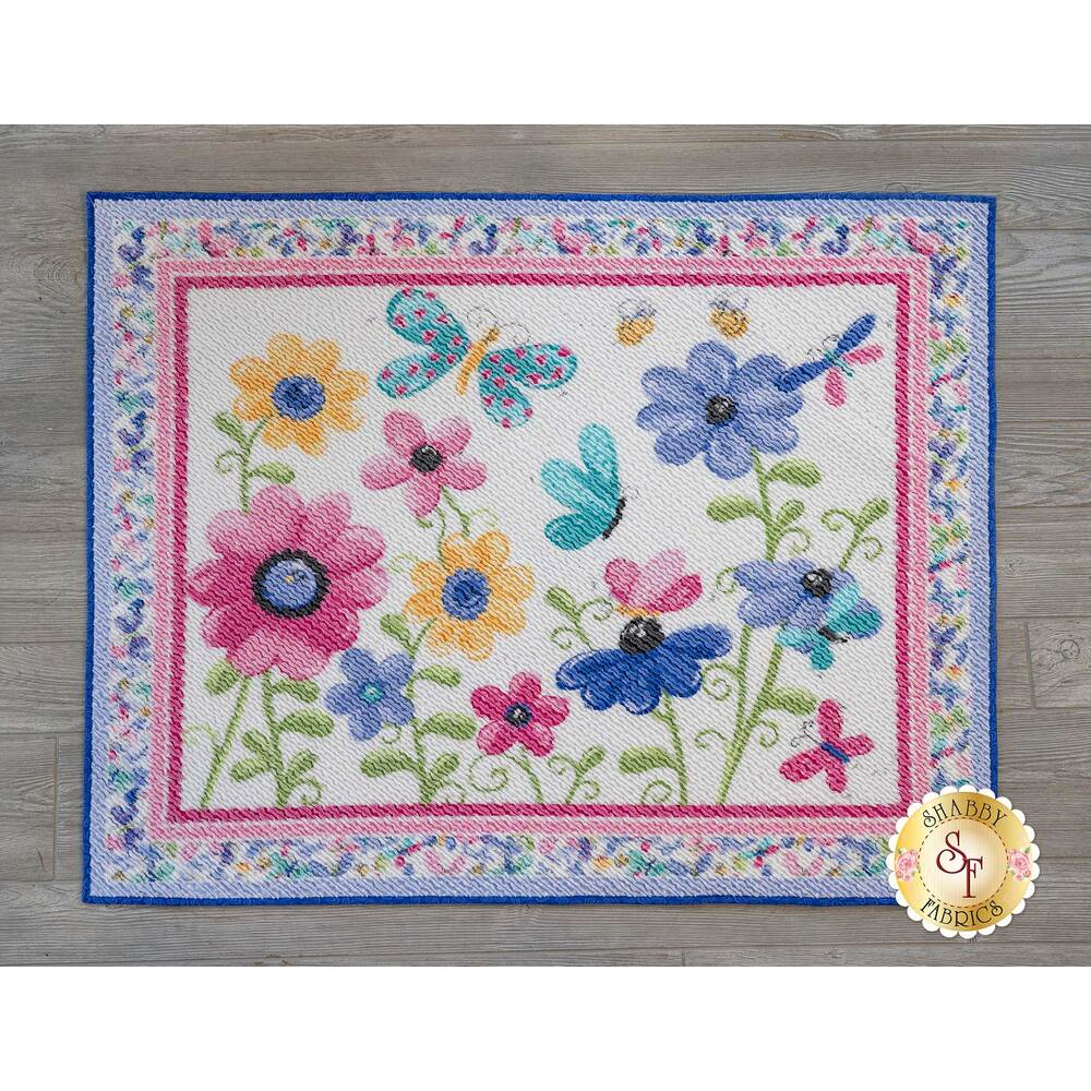 The beautiful Flutter The Butterfly Chenille Rug displayed on a wood floor | Shabby Fabrics