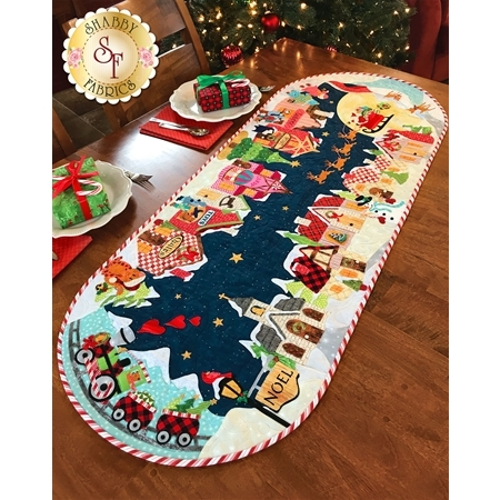 Angled view of an applique Christmas village table runner with cozy snow-covered shops.
