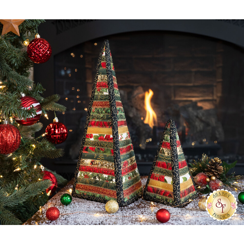 The large and small Christmas Tree fully assembled and displayed in front of a fireplace