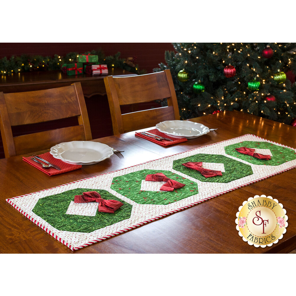 Angled view of a white table runner with red polka dots featuring four patchwork wreaths with bows.
