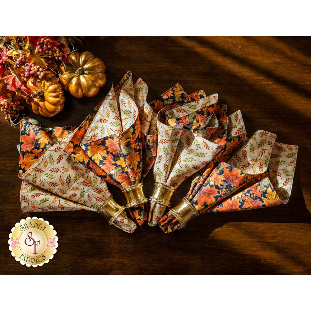 4 Fall themed Cloth Napkins displayed on a dark wood table